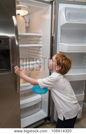 Hungry little boy looking into empty fridge