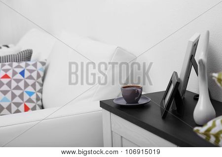 Cup of coffee on commode in room