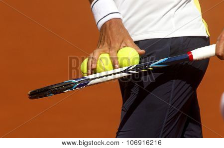 A tennis player checks balls for serve a tennis ball during a match
