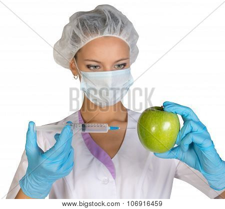 Woman holding an apple and is injected with a syringe. Genetically modified foods