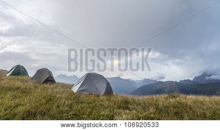 panorama of the mountains, in a clearing, there are three tents