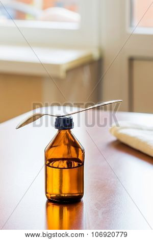 Cough Syrup Bottle With Spoon Close Tothe Window