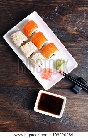 Delicious rolls, ginger, wasabi and soy sauce on wooden background