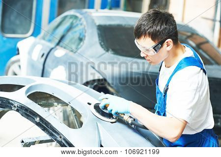 auto mechanic worker sanding bumper car at automobile repair and renew service station shop by grinder machine