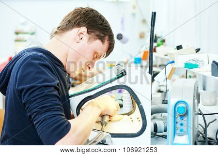 Male dental technician working with tooth dentures at prosthesis laboratory
