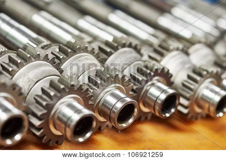 close-up metal shafts with cog wheels gears at industrial factory