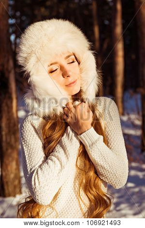 Happy Cute Girl Wearing White Fur Hat In Winter Forest Shutting Her Eyes