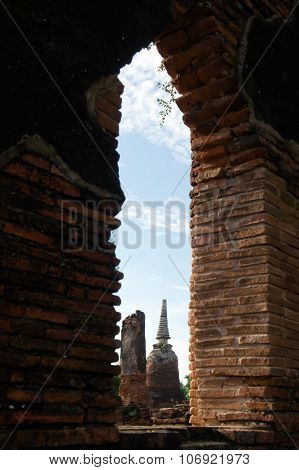 Window view of Old pagoda with cloudy sky in Thailand