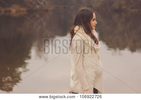 dreamy pregnant woman in cozy warm outfit on the walk on riverside in autumn