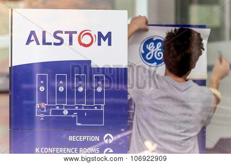 Baden, Switzerland. 31st October 2015. Alstom logos being removed by worker to install GE logos before merger and acquisition of General Electric on 2nd November 2015.
