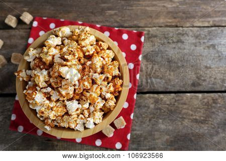 Sweet caramel popcorn in a bowl on red cotton napkin against wooden background