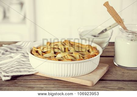 Homemade apple pie on wooden table, on light background