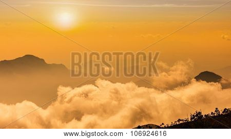 Panorama of mountains in clouds on sunset