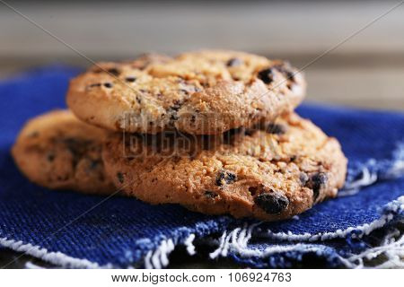 Cookies with chocolate crumbs on wooden table against blurred background, close up
