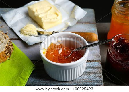 Tasty jam in the jar and bowl, butter and fresh bread on wooden background close-up