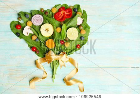 Cute bouquet of sorrel decorated with vegetables and fruits on blue wooden background