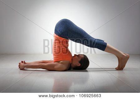 Beautiful sporty fit yogini woman practices yoga asana Halasana - plow pose