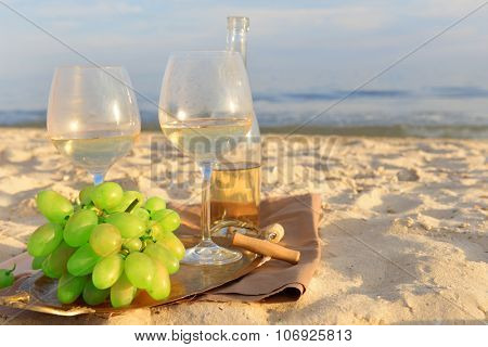 Romantic composition of white wine and grape on sandy beach