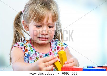 Unhappy Little Girl Playing With Wooden Blocks.