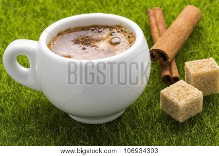 Coffee hot cup and cinnamon sticks with cubes brown cane sugar on the grass.