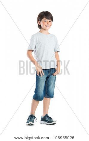 Smiling little boy with freckles standing isolated on white background. Portrait of satisfied cute child in casual clothes looking at camera with hand in pocket standing against white background.