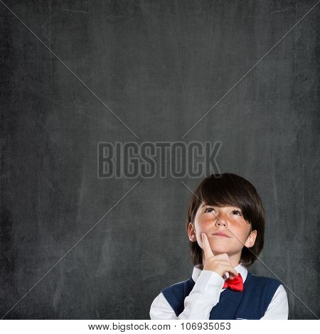 Closeup shot of boy thinking with hand on chin isolated on blackboard. Portrait of pensive child thinking about his academic future. Child have an idea.