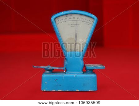 Old Worn Blue Weighing Scale On Red Background