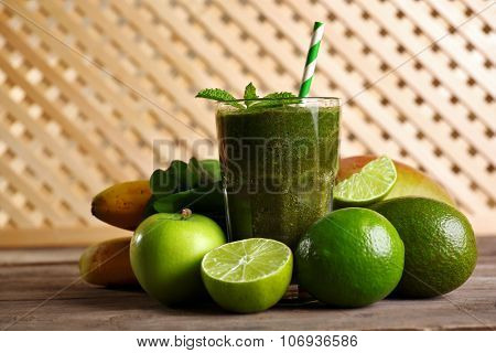 Green healthy juice with fruits and herbs on wooden background