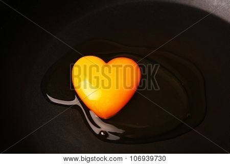 Scrambled egg in heart shape on black pan background