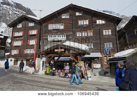Tourists walk by the street in Zermatt, Switzerland. Wooden Houses Of Zermatt.