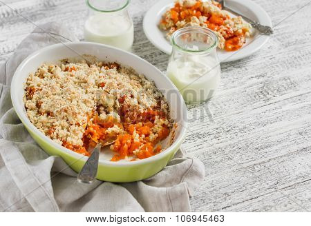 Pumpkin Casserole In A Ceramic Baking Dish And Natural Yoghurt In Glass Jars On A White Wooden Table