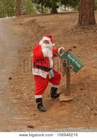 Santa checking the mailbox for mail at the North Pole, which has no snow due to global warming