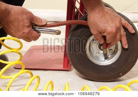closeup of Mechanic putting air in the small tire of a hand cart