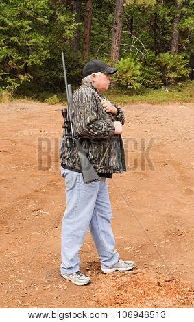 Hunter demonstrating the sling method to safely carry a firearm while hunting, the choice of the correct method depends on the situation