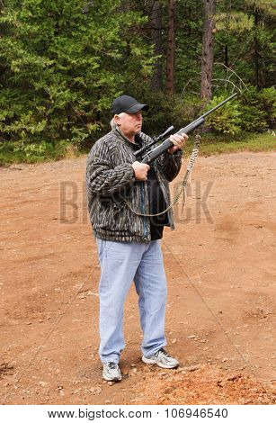 Hunter demonstrating the two handed method to safely carry a firearm while hunting, the choice of the correct method depends on the situation