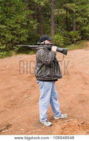Hunter demonstrating the over the shoulder method to safely carry a firearm while hunting, the choice of the correct method depends on the situation