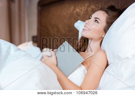 Young beutiful woman lying in her bed with white sheets and dreaming holding her book