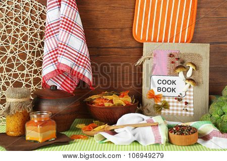 Decorated composition of cookery book and kitchen equipment on wooden background