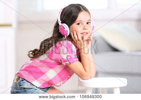 Pretty smiling little girl listening music with pink headphones in light room