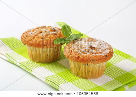 close up of two chocolate chip muffins on checkered dishtowel