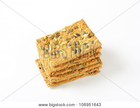 stack of pumpkin seed crispbread on white background