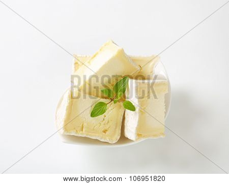 bowl of sliced soft white rind cheese on white background