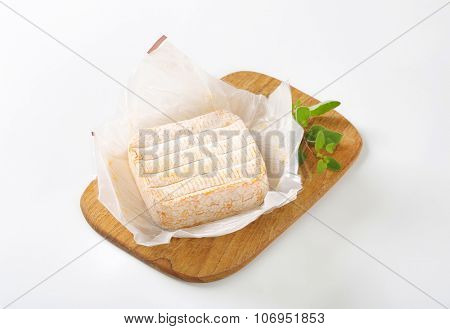 unwrapped soft white rind cheese on wooden cutting board