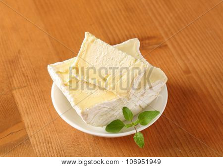 sliced soft white rind cheese on white plate