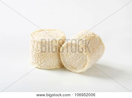two soft white rind cheeses on white background