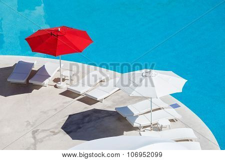 Sun Umbrellas And Beds Near Swimming Pool At Poolside