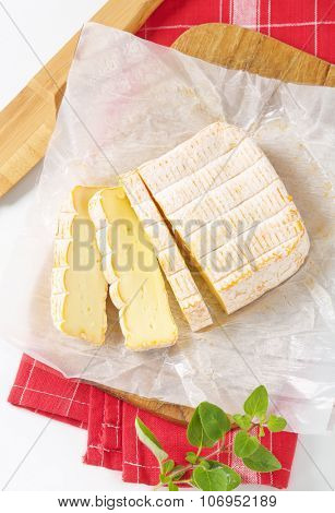 sliced soft white rind cheese on wooden cutting board