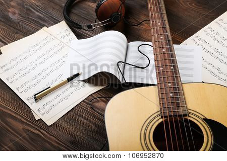 Guitar with earphones and music sheets on wooden background
