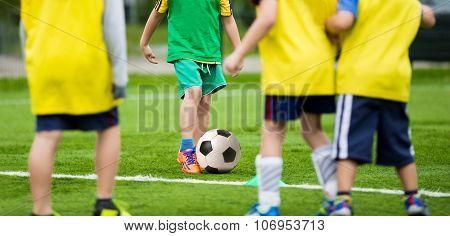 Kids boys playing football soccer match on sports field
