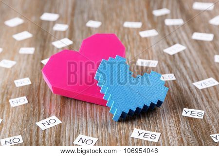 Two hearts with yes and no on wooden background
